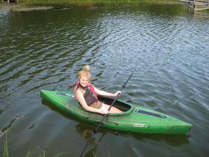 Daughter Emma kicks back in a kayak.